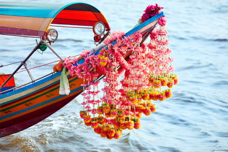 Traditional Thai longtail boat with flower garland close up in Chao Phraya river in Bangkok