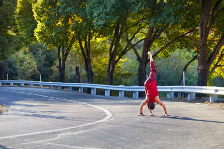 Fit man in red costume doing yoga on the asphalt road in Almaty, Kazakhstan