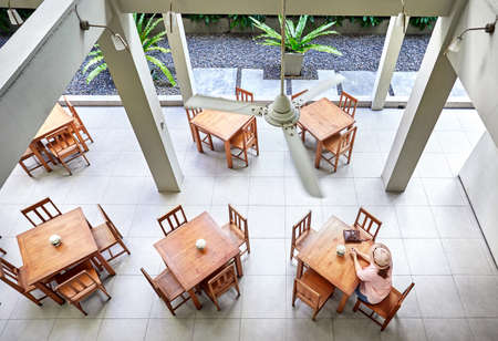 Woman in pink shirt and hat sitting at the table in hotel restaurant. Aerial view.