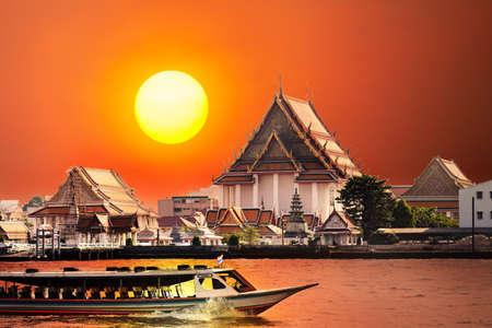 Speed boat at Chao Phraya River near Wat Arun at red sunset sky in Bangkok, Thailand