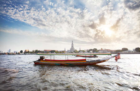 Traditional Thai Long tail boat in Chao Phraya river near Wat Arun at sunset in Bangkok, Thailand