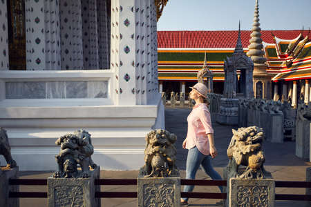 Beautiful tourist woman in hat and pink shirt walking in Wat Arun temple at sunset in Bangkok, Thailand Stock Photo