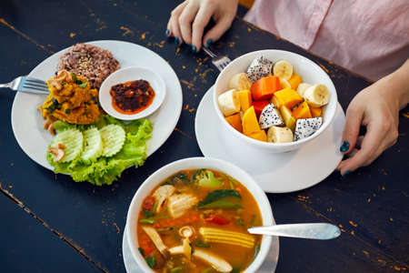 Thai traditional sour soup Tom Yam in vegetarian variation, curry rice and fruit salad in vegan restaurant in Bangkok