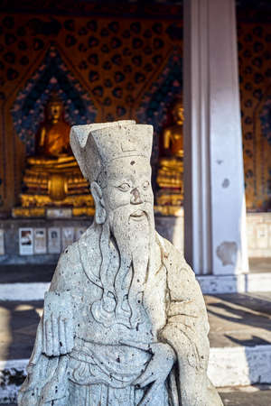 Stone statue of monk in Buddhist Temple Wat Arun in Bangkok, Thailand Stock Photo