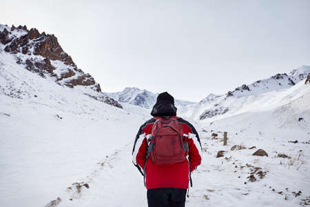 Hiker with red backpack walking around snowy mountain. Freedom of trekking concept. Stock Photo