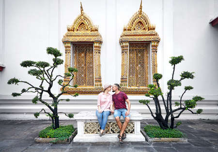 Young Couple in red clothes sitting on the bench near decorative trees and golden windows of Wat Pho in Bangkok, Thailand Stock Photo
