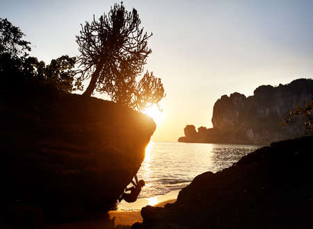 Rock climber in silhouette at Tonsai beach at sunset in Krabi, Thailand 報道画像