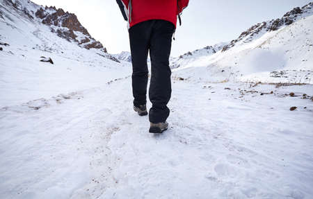 Hikers legs walking around snowy mountain. Freedom of trekking concept.