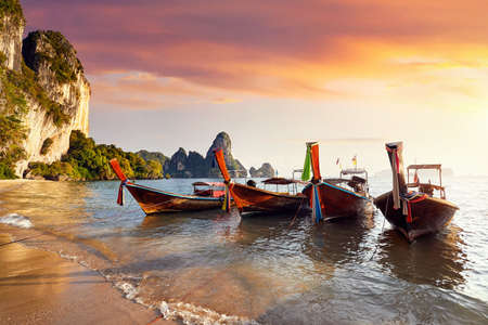Long tail boats on tropical Tonsai beach at beautiful sunset in Krabi, Thailand