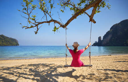 Tourist woman in pink dress on the swing at tropical beach of Hong Island in Andaman Sea, Thailand