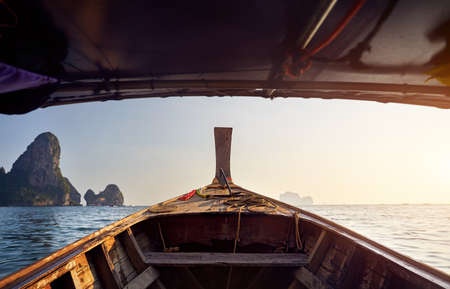 Cruise at long tail boat with view to tropical islands at sunset in Andaman Sea, Thailand