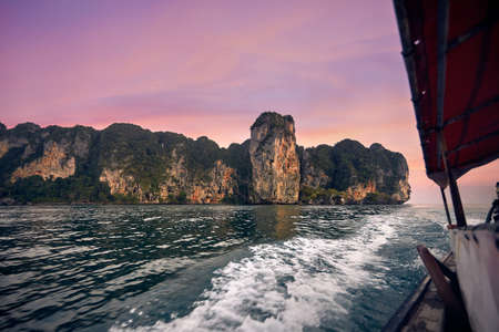 Cruise at long tail boat with view to tropical islands at pink sunset in Andaman Sea, Thailand