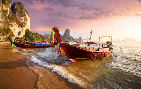 Long tail boats on tropical beach at beautiful sunset in Thailand