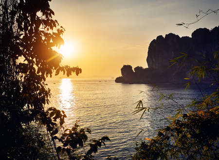 Beautiful tropical bay with sandy beach and rock at sunset in Andaman Sea, Thailand