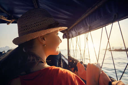 Portrait of woman at long tail boat with view of tropical islands at sunset in Andaman Sea, Thailand Stock Photo