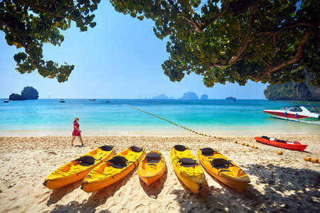 Woman in pink dress walking on the Phranang beach with yellow kayak boat in Thailand  Stock Photo