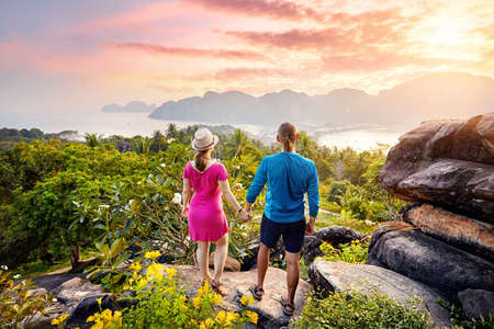 Happy couple on the tropical Phi Phi island at sunset in Southern Thailand. Travel magazine concept. 스톡 콘텐츠