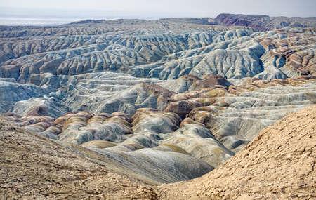 Bizarre layered mountains in desert park Altyn Emel in Kazakhstan Фото со стока