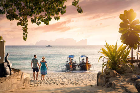 Happy couple on the tropical beach of Phi Phi island at sunset in Southern Thailand. Travel magazine concept. Imagens