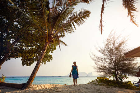Woman near coconut palm tree at the tropical beach on Phi Phi Island in Southern Thailand.