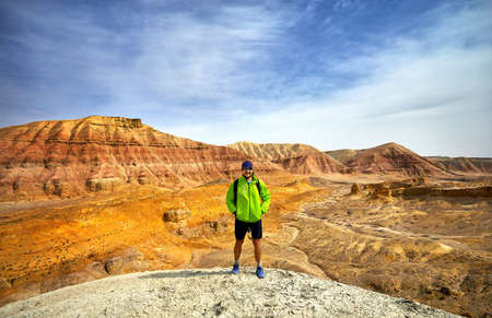 Tourist in green jacket with surreal red and yellow mountains at background in desert park Altyn Emel in Kazakhstan Stock Photo