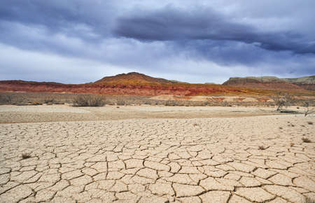 Dry cracked ground in Desert Park and rainy clouds above mountains Stock fotó