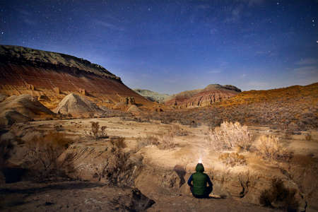 Man with head light sitting on the ground in the desert at night sky background. Travel, adventure and expedition concept.