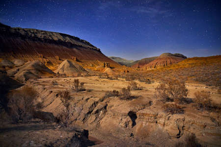 Red mountains in the canyon desert at night starry sky background. Astronomy photography of space and landscape. Stock Photo