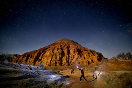Man with head light in the desert at night sky background. Travel, adventure and expedition concept. Imagens - 99338239
