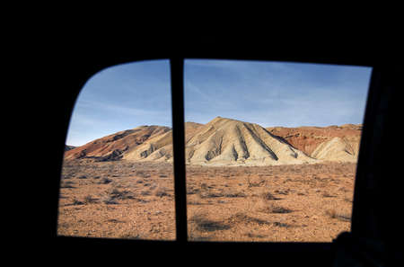 Bizarre dry mountains in the desert. View from car. Nature Park Altyn Emel in Kazakhstan