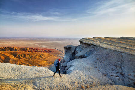Tourist walking at the on surreal white mountains in desert park Altyn Emel in Kazakhstan Stock Photo