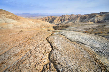 Landscape of cracked ground and mountains in the desert. National desert park Altyn Emel in Kazakhstan Zdjęcie Seryjne