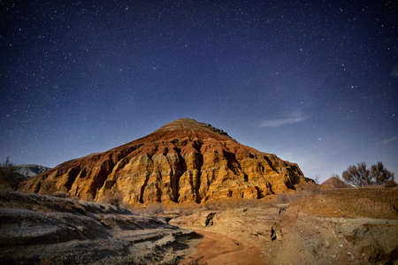 Red mountain of pyramid shape in the desert at night starry sky background. Astronomy photography of space and constellations. Stock fotó