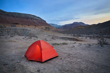 Touristic orange tent in the Desert mountains at sunrise in Kazakhstan