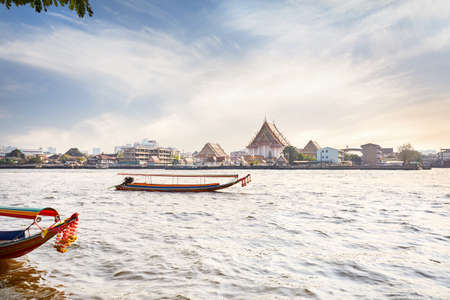 Traditional Thai Long tail boat in Chao Phraya River near Wat Arun at sunset in Bangkok, Thailand Stock Photo