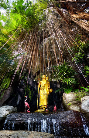 Golden Buddha statue in the tropical garden with waterfall in Wat Saket Golden Mountain Temple in Bangkok. Vertical position cover Stock Photo