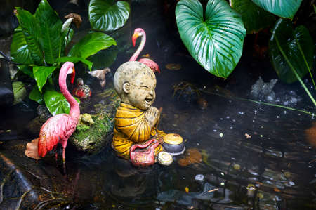 Statue of little Buddhist monk in the tropical garden with pink flamingo in Wat Saket Golden Mountain Temple in Bangkok