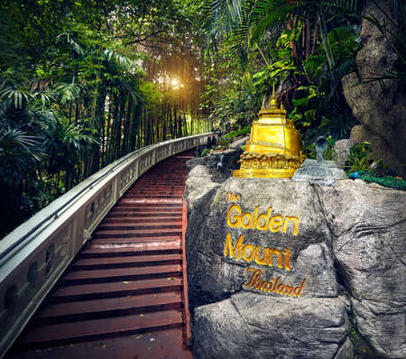 Golden Stupa statue in the tropical jungle near the stairs in Wat Saket Golden Mountain Temple famous Landmark in Bangkok, Thailand