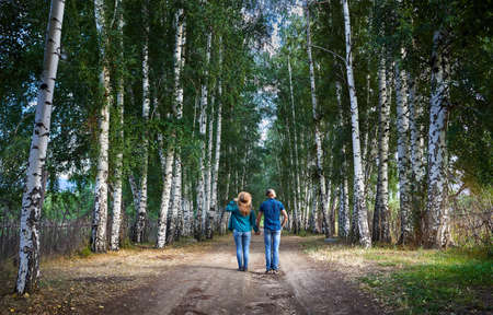 Happy couple in checked shirts on the road in birch wood in Kyrgyzstan. Romantic date in the forest.