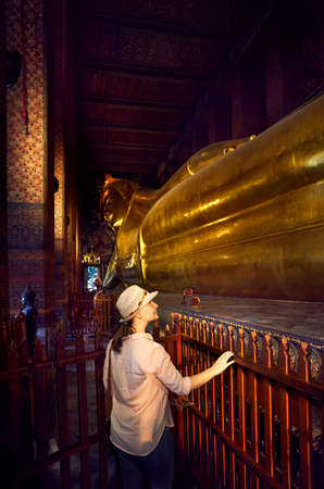 Woman tourist near Statue of Big Golden Buddha in wat Pho temple in Bangkok, Thailand. Symbol of Buddhist culture.