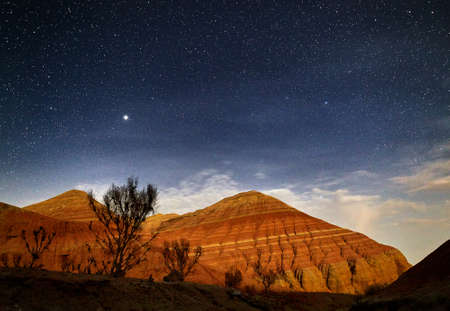 Red mountains in the canyon desert at night starry sky background. Astronomy photography of space and landscape. Stock fotó