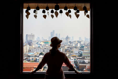 Silhouette of tourist woman looking in window to Bangkok city view of skyscrapers business district from Golden Mountain Pagoda Wat Saket at overcast sky background. Stock Photo