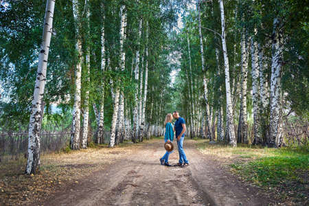 Happy couple in checked shirts hugging on the road in birch wood in Kyrgyzstan. Romantic date in the forest. Stock Photo