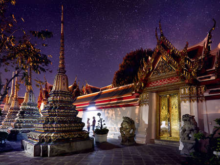 Young Couple in Buddhist temple complex Wat Pho in Bangkok at magical night starry sky at background in Thailand Stock Photo