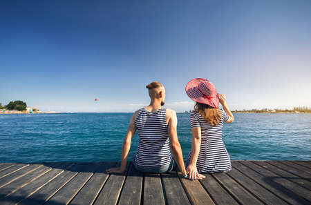 Romantic couple in striped dress sitting on pier and looking at blue Lake Issyk Kul in Kyrgyzstan. Summer and Sea concept. Stok Fotoğraf