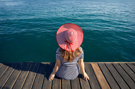 Woman in hat and striped dress sitting on pier and looking the emerald blue sea. Summer and Sea concept.