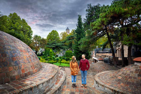 Tourist woman in brown jacket and man in red shirt standing near the dome of Public Sulfuric bath district in central Tbilisi, Georgia