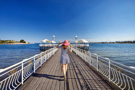 Tourist woman in red Hat and striped dress standing on the pier in Ruh Ordo cultural complex Issyk Kul lake with mountains background at sunset in Cholpon Ata, Kyrgyzstan