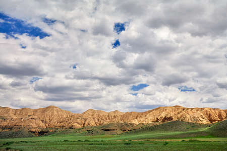 Yellow mountains of moon canyon in green steppe in Kazakhsthan