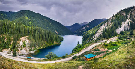 Panorama of mountain Lake Kolsai in the mountains with fir forest in Kazakhstan
